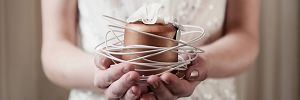 bride holding bronze mini wedding cake in hands
