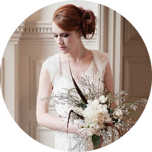 bride in Jenny Packham dress holding wold bouquet with feathers