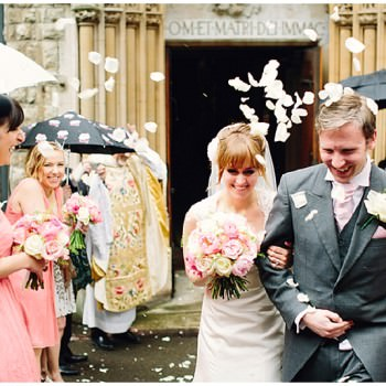 bride and groom exit church under confetti