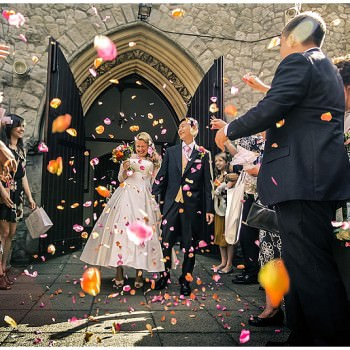 bride and groom leave church under a shower on confetti