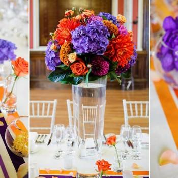 orange and purple wedding flowers on long table