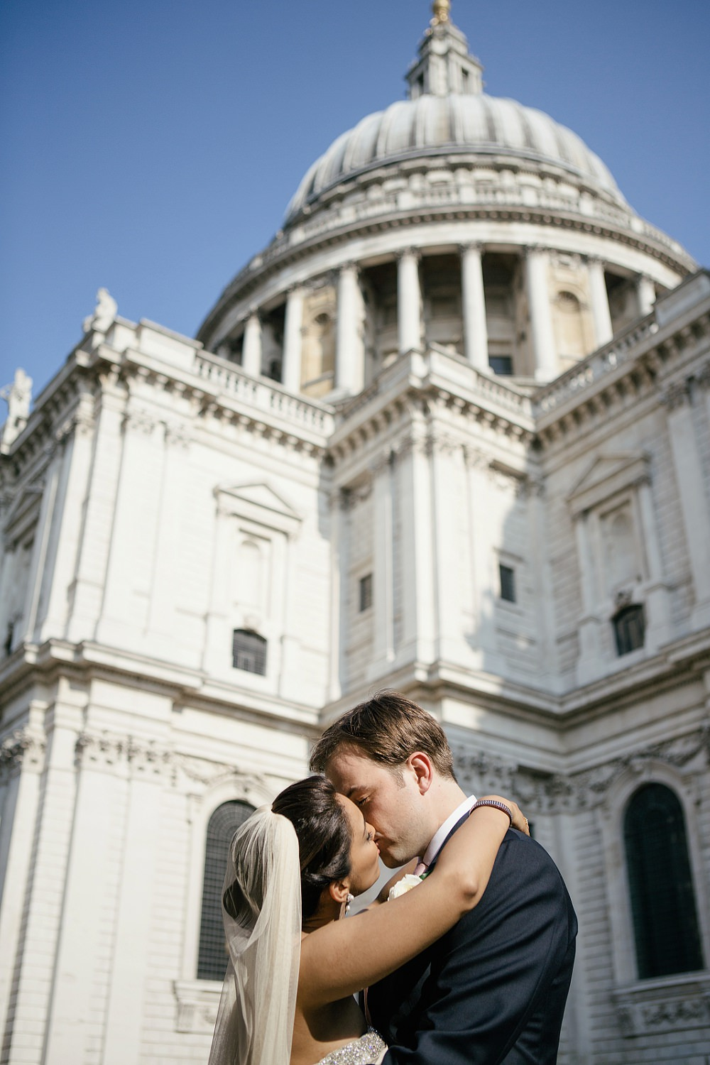 Brie and groom kissing in front of St Pauls Cathedral