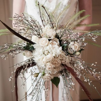 blue sky flowers organic textured wedding bouquet with foliage and pheasant feathers