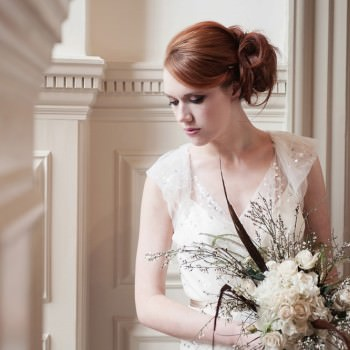 bride with red hair soft updo with fern folaige feather wedding bouquet