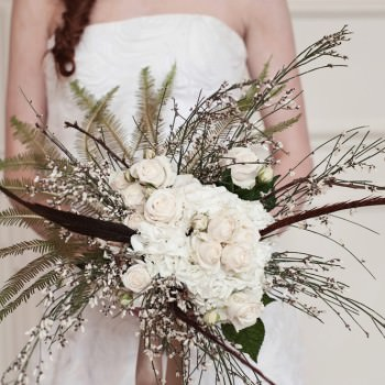 gold fern with feathers and white roses wedding bouquet