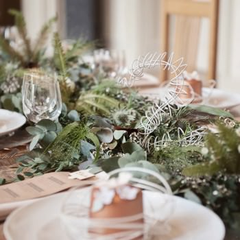 fern and eucalyptus foliage wedding table runner with feathers