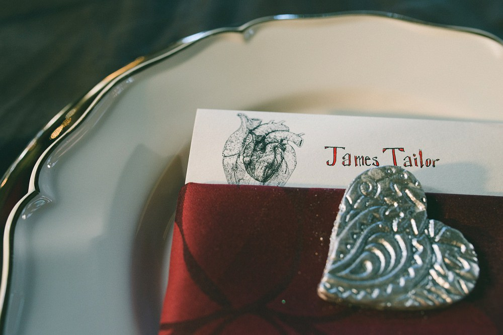 wedding table setting with red napkin and silver heart cookie