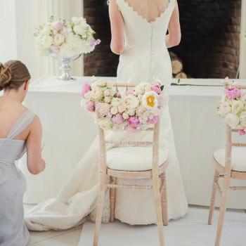 bridesmaid adjusts birdess dress during ceremony