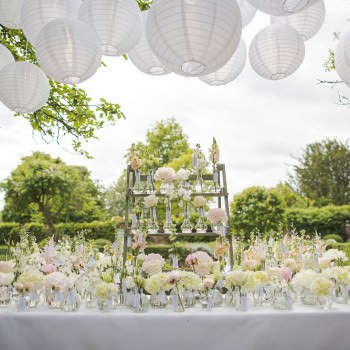 wedding escort card table with small bottles and pretty flowers