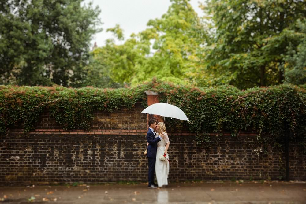 Bride and groom in the rain with white umbrella | London Wedding The Curries Photogrpahy | Always Andri Wedding Planning