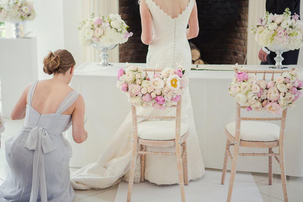 bridesmaid in grey dress fixes brides train at wedding   Marianne Taylor Photography