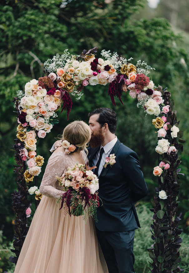 autumnal blush red and coral floral wedding arch