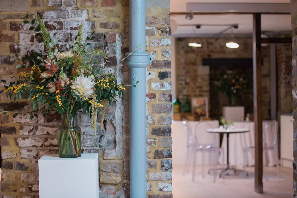funky brickwedding venue with autumnal flowers