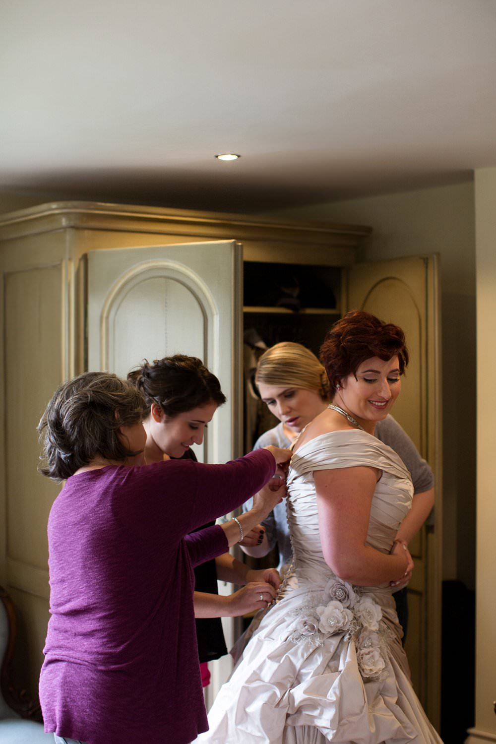 Bride being dressed on morning of her wedding by her mum and bridesmaids