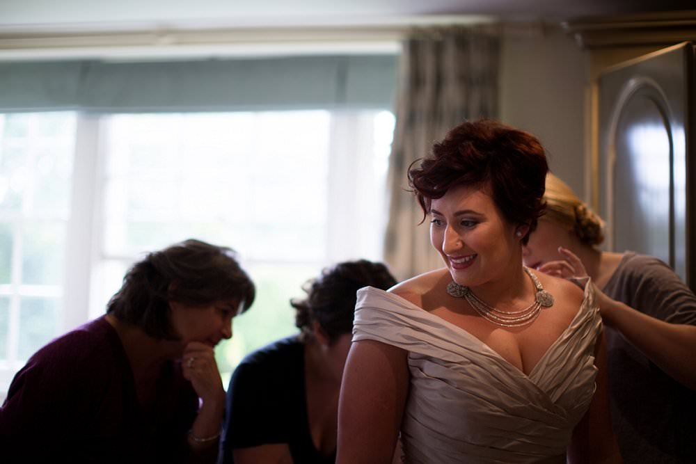 Bride being dressed on morning of her wedding looking happy