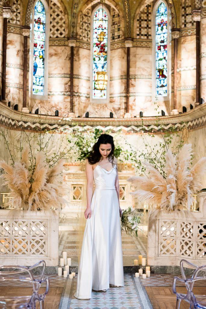 Fitzrovia Chapel wedding photoshoot but Always Andri Wedding Design bride in simple sating wedding dress at altar
