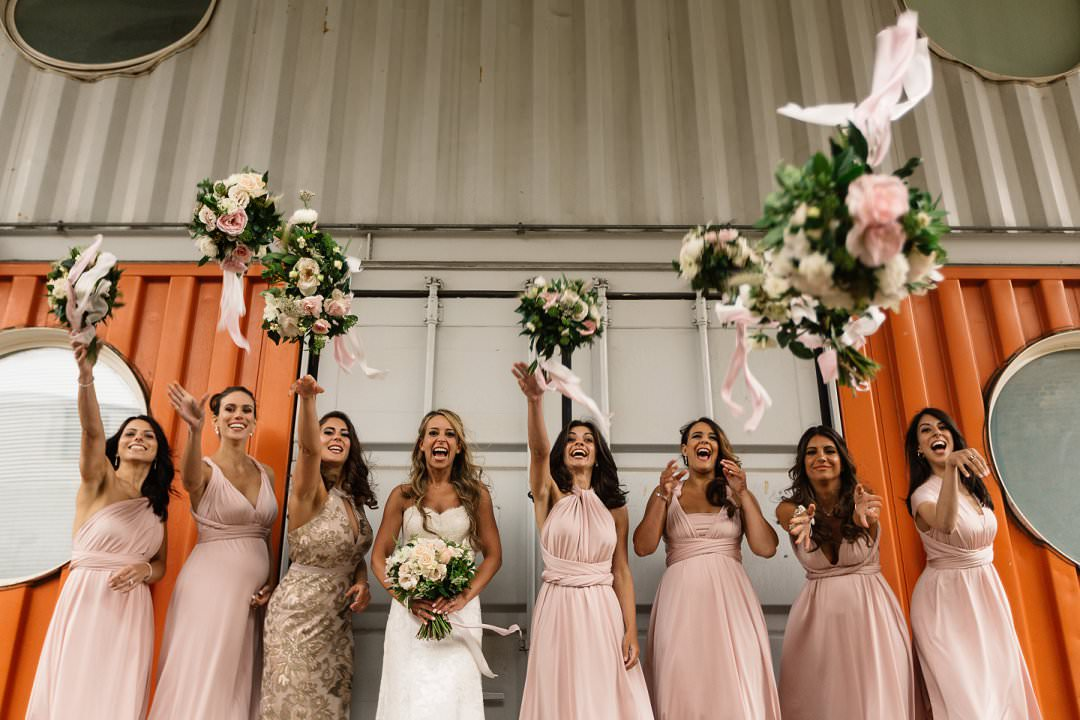 bridesmaid in blush pink  dresses throw bouqets in air, wedding planner london
