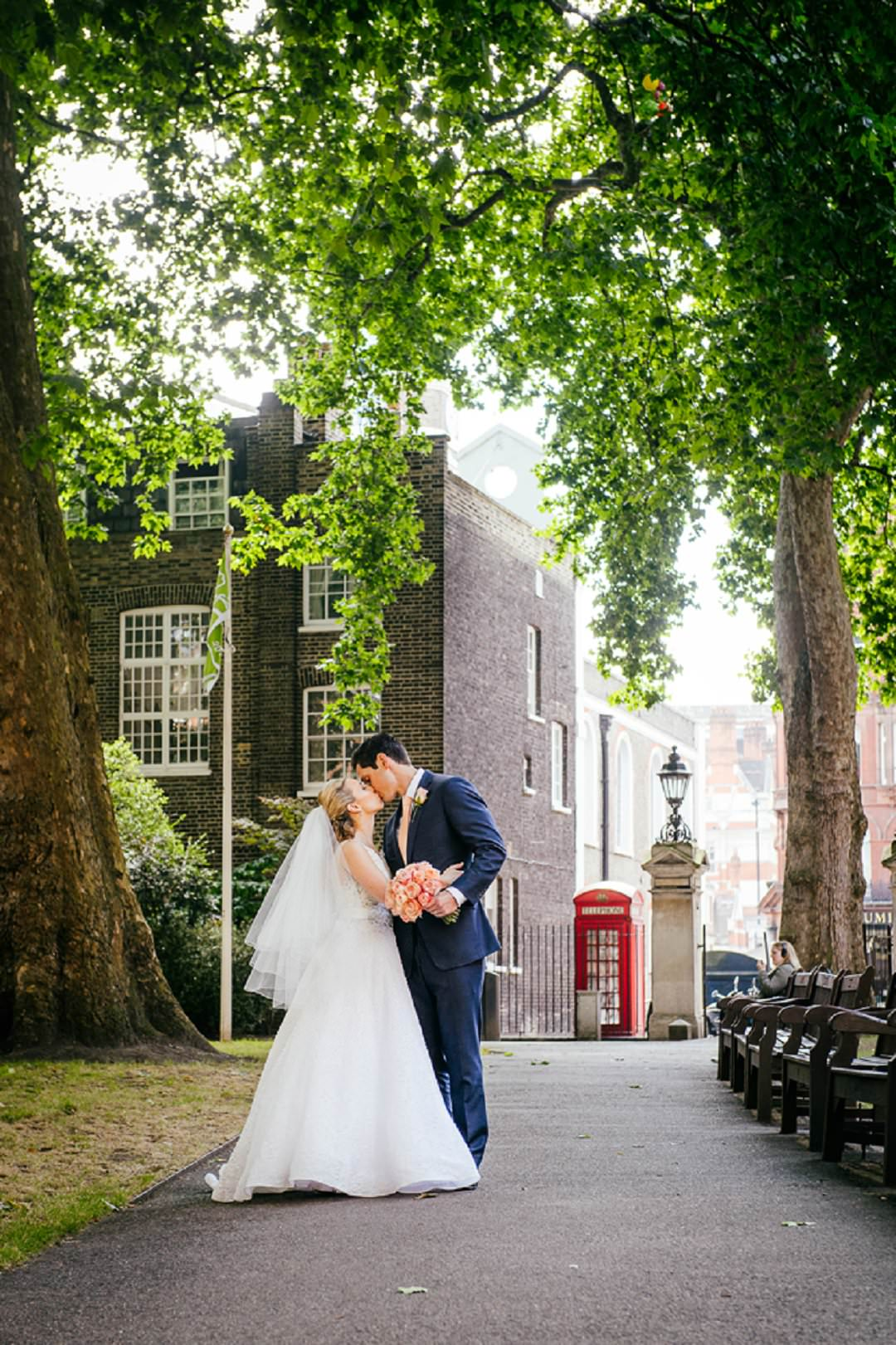bride and groom in park with red telephone box in central London