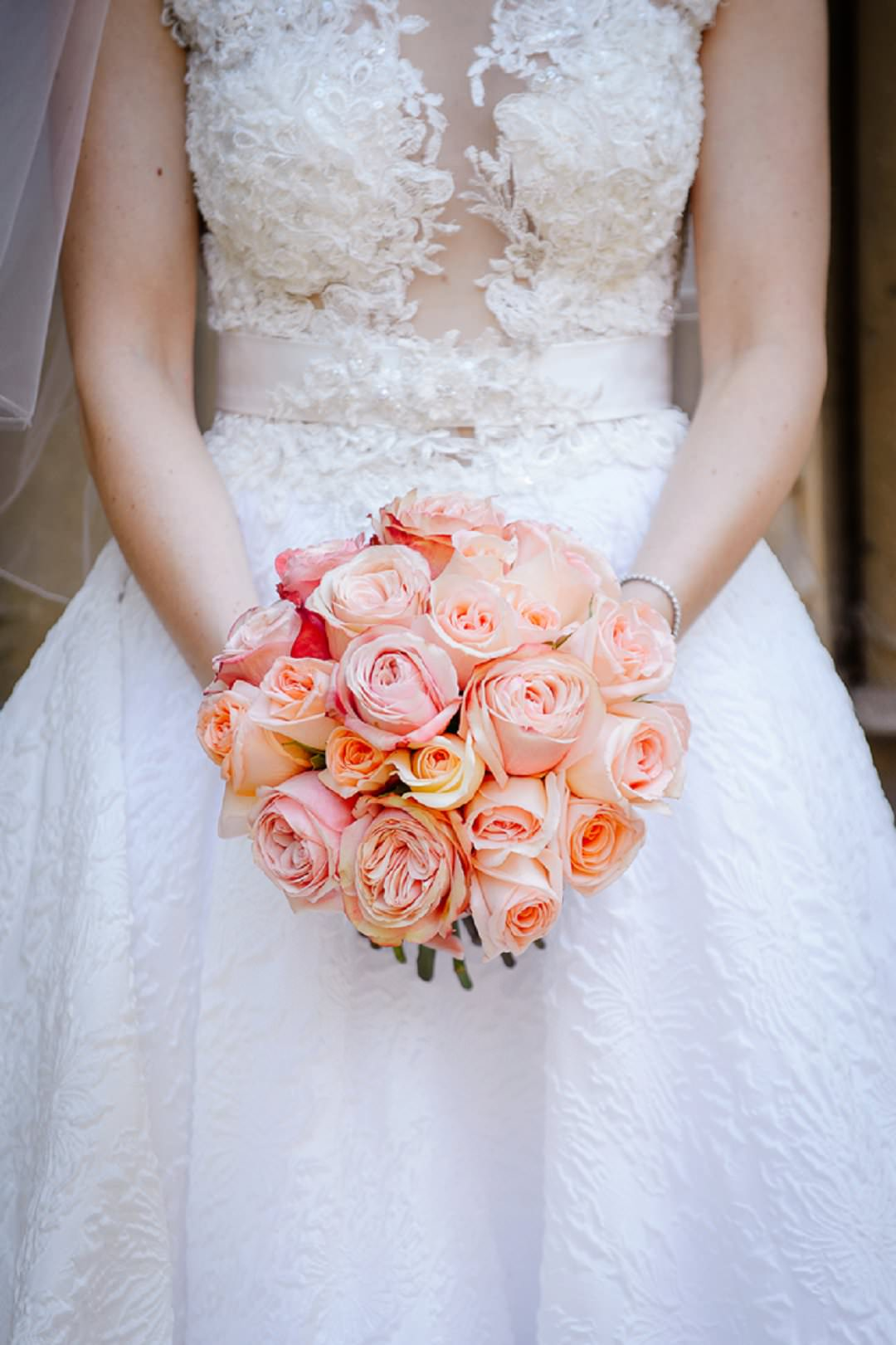 peach roses bouquet held by bride