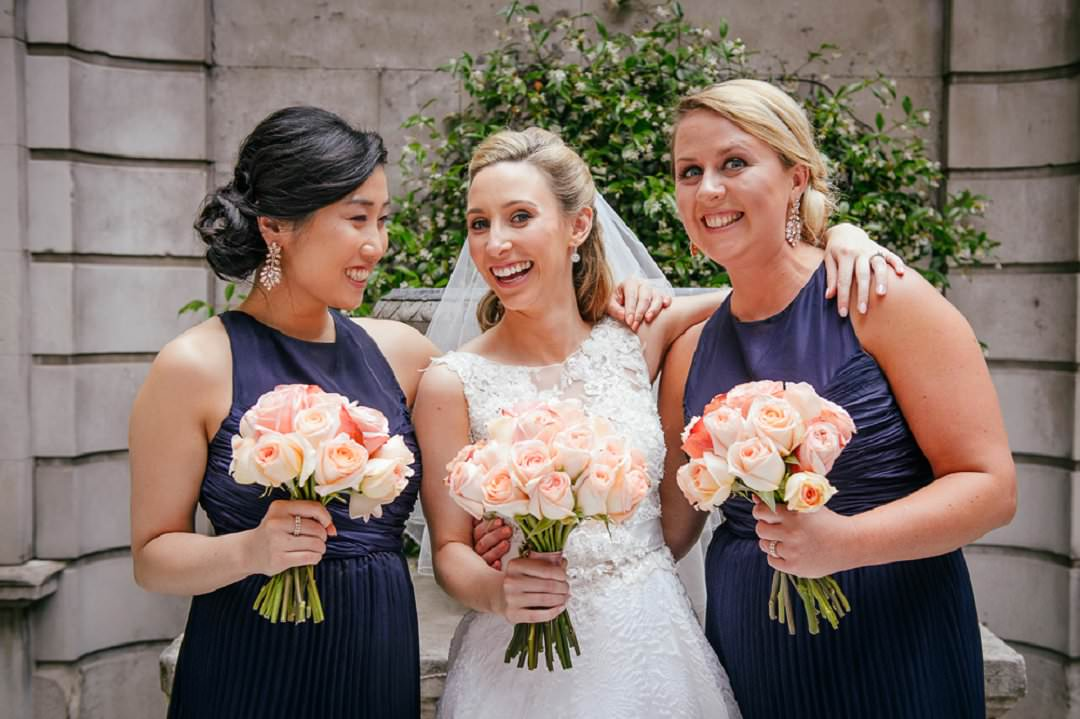 bride with bridesmaids in navy holding peach bouquets