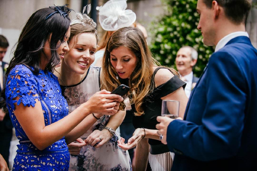 guests looking at phone at Dartmouth House London Wedding