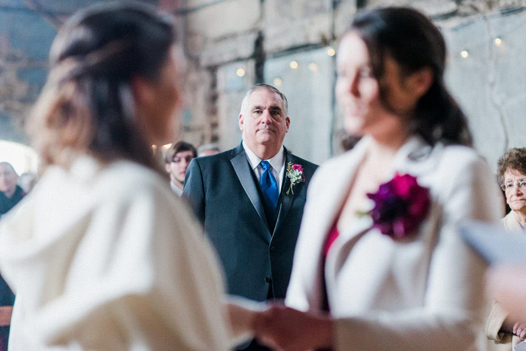 wedding guest looking at happy couple during ceremony