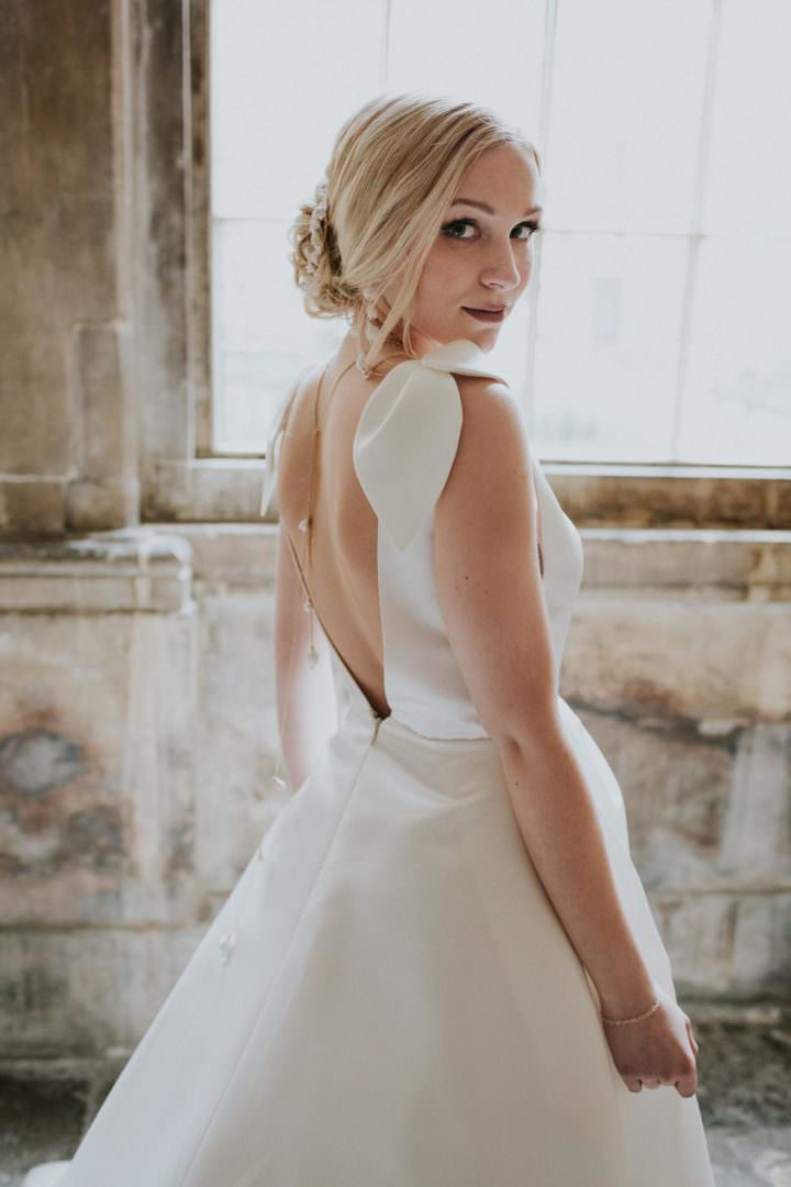 bride in low v back wedding dress and gold back necklace