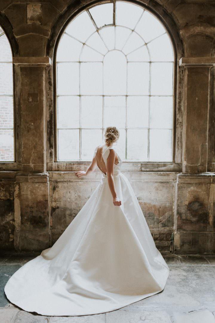 bride in Jesus Piero weddign dress looking out of window at london wedding venue the Charterhouse