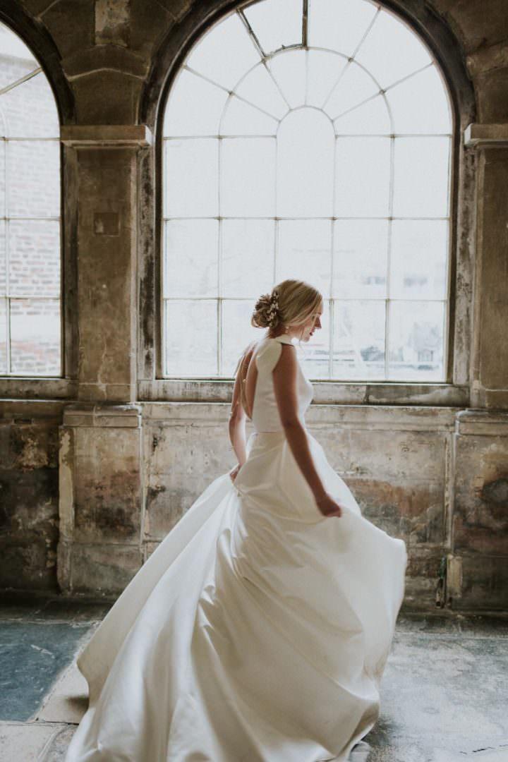bride in Jesus Piero weddign dress twirling around in dress at London wedding venue the Charterhouse