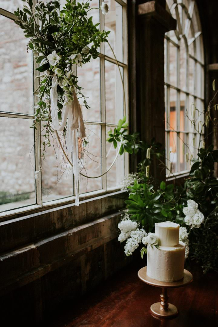 buttercream wedding cake in window with brass foliage hoop  at London wedding venue the Charterhouse