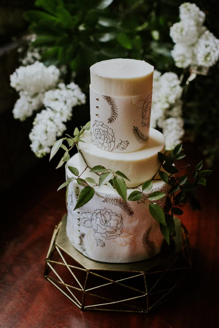 three tiered buttercream wedding cake with botancil drawing
