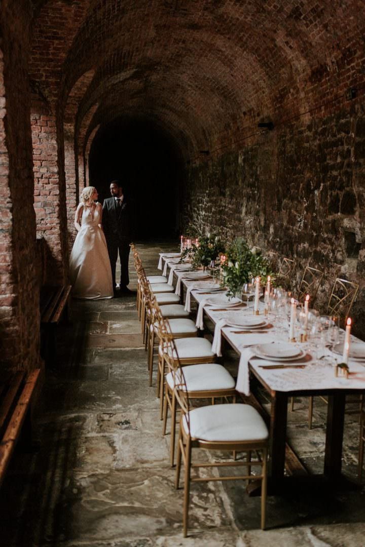 long wedding dining table in cloister with taper candles bride and groom looking outside window at London wedding venue the Charterhouse