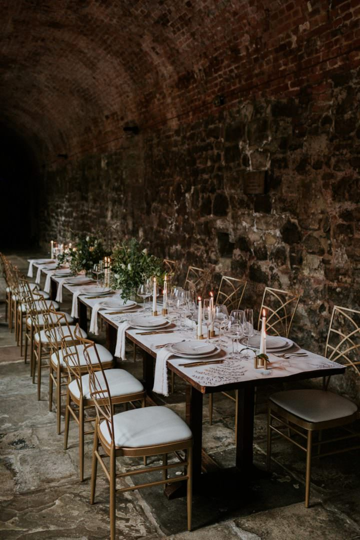 long wedding dining table in cloister with taper candles at London wedding venue the Charterhouse