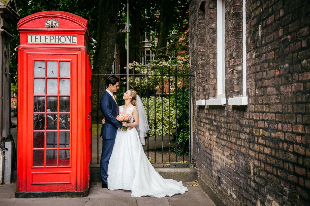 bride and groom standing next to iconic red telephone box in London