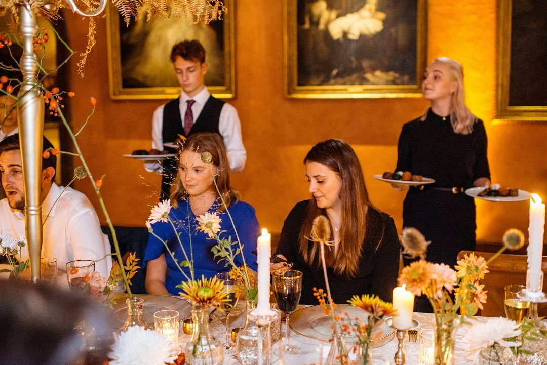 wedding catering caper and berry waiter serves food to waiting diners
