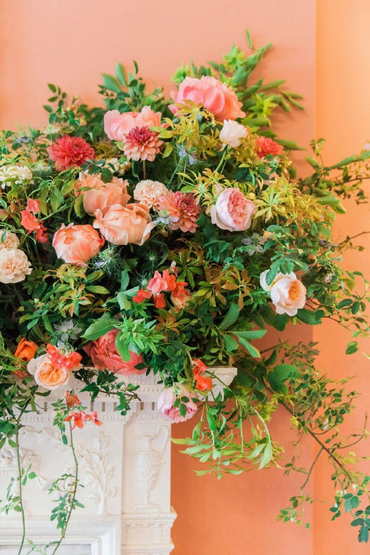 coral and peach wedding flowers on fireplacewith cascading foliage