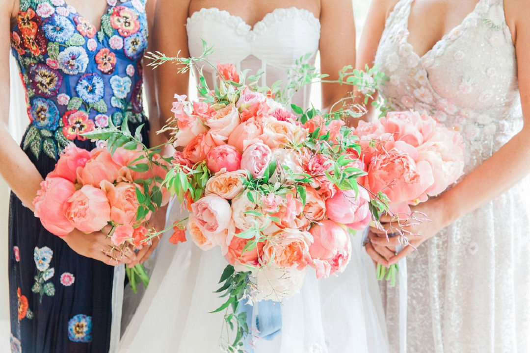 coral and peach wedding bouquets being held by bride and bridesmaids