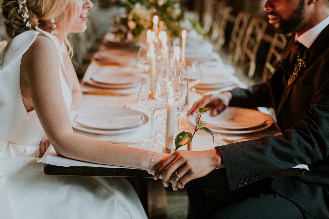 bride and groom hold hands at dining table