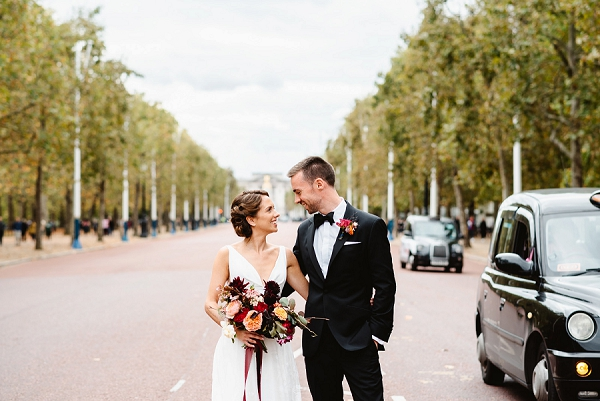 Brie and groom standing on the Mall while black London taxi passes